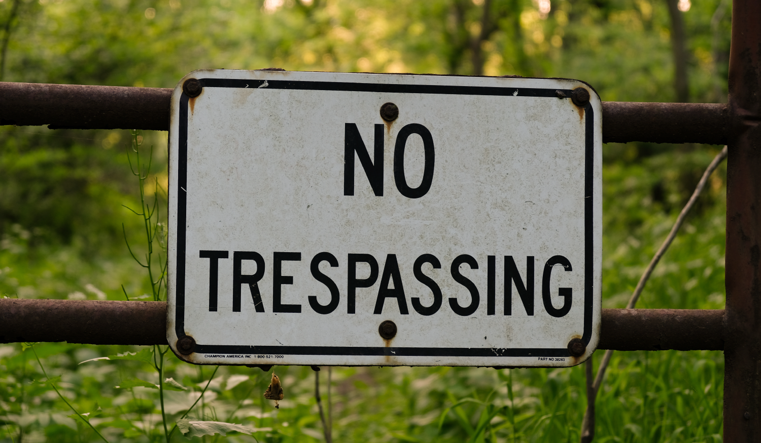 Photo of a no trespassing sign on gate on hunting land
